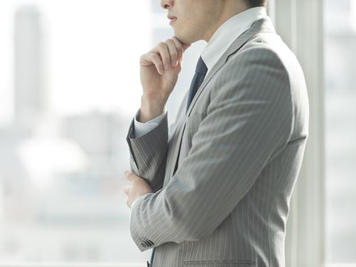 窓際で考えるビジネスマン