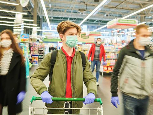 感染症対策をしてスーパーで買い物をする人々
